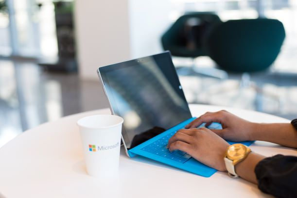 Microsoft Surface Pro tablet with Blue Keyboard  next to a Microsoft cup with a Person Typing on the Keypad