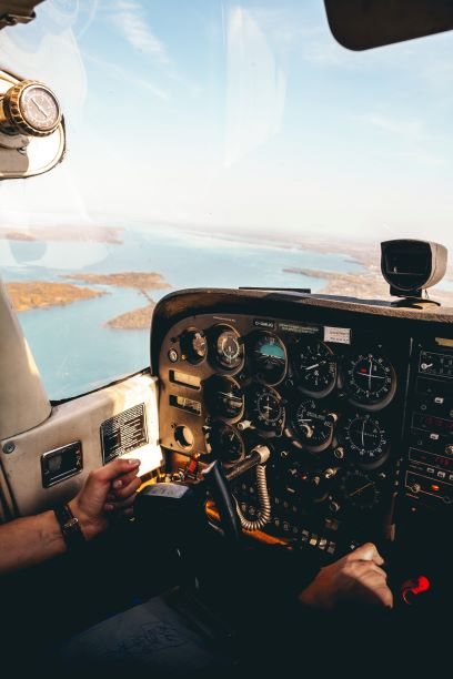 The view from a windshield inside the cockpit of a pilot. A landscape of a lake and land.