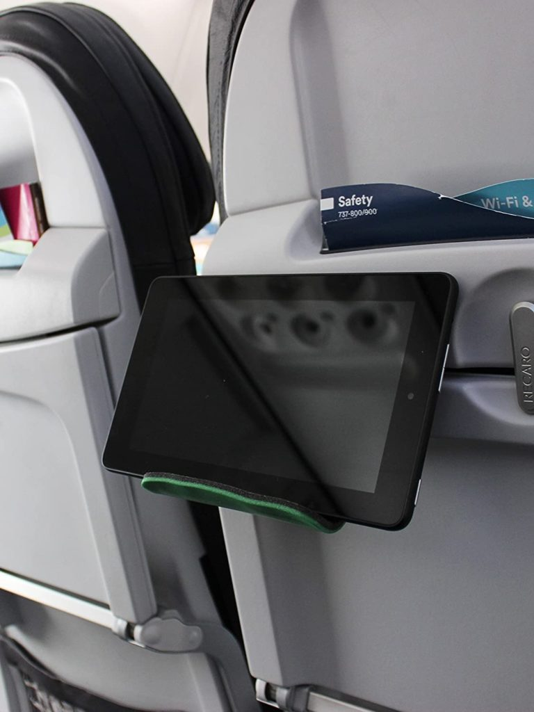 The Flip Flap holder for mobile devices attached to the front seat on an airplane.