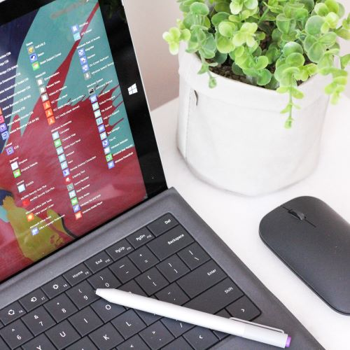 Black Microsoft Tablet with Keypad next to a Flower Pot on a Table with a White Pen and a Black Mouse