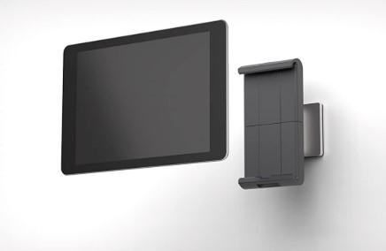 The adjustable grip attached to the wall with an iPad in front of it