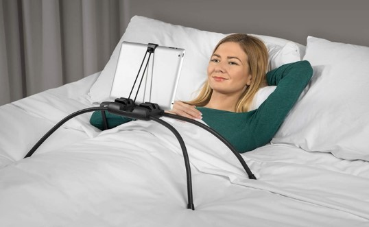 Woman using a tablet stand in bed